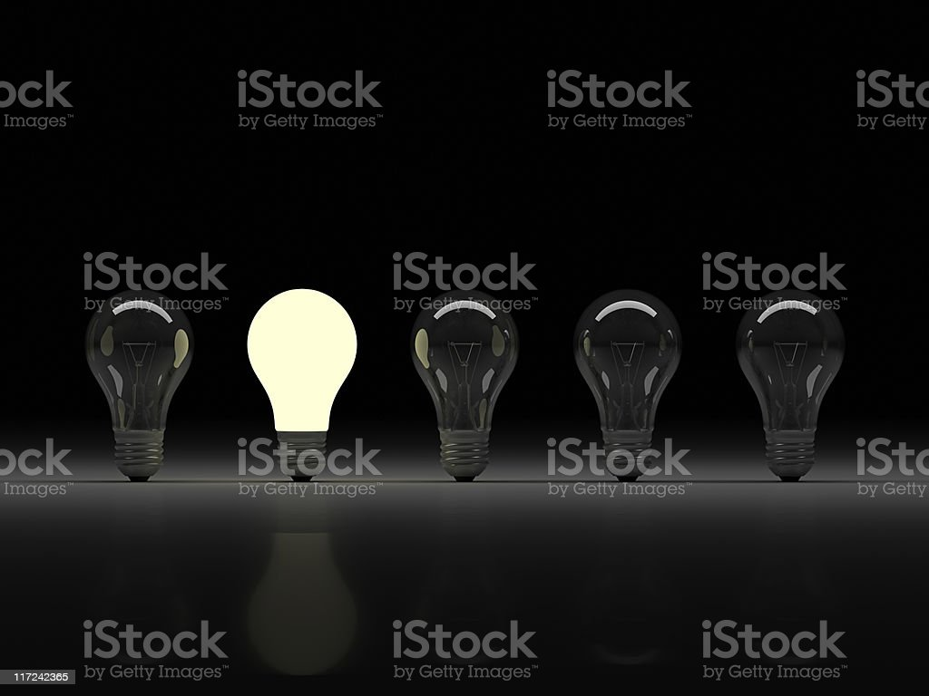 A row of five light bulbs on a black background, 2nd is lit stock photo