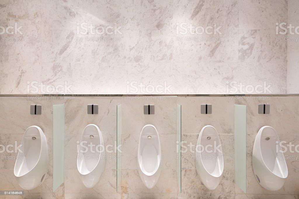 Row of five urinals in men's public toilet stock photo