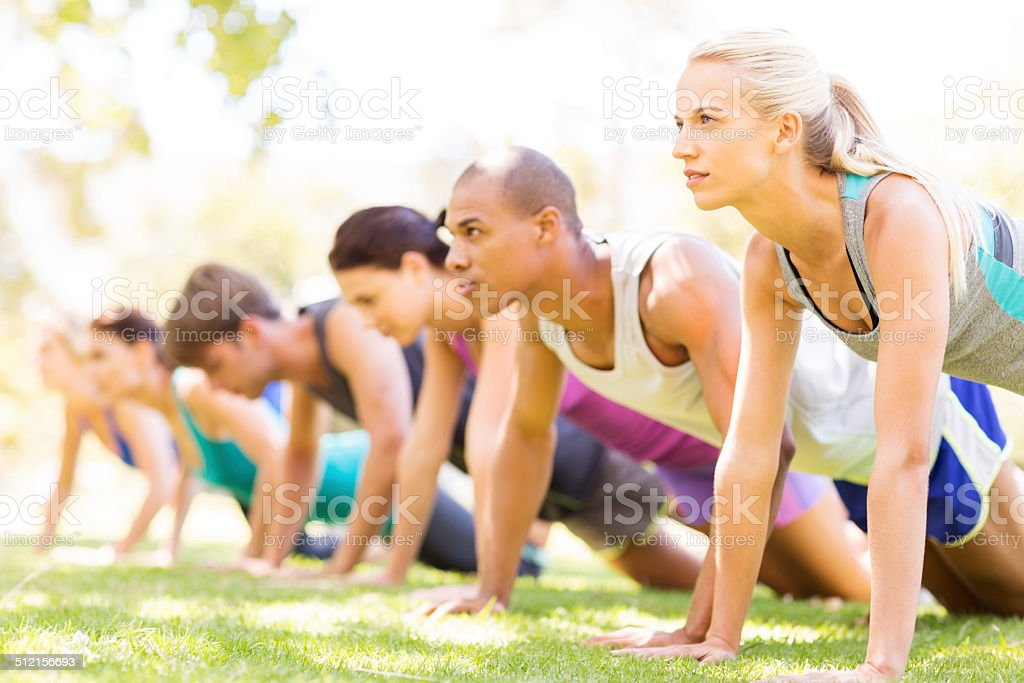 Row Of Friends Doing Push-Ups In Bootcamp stock photo