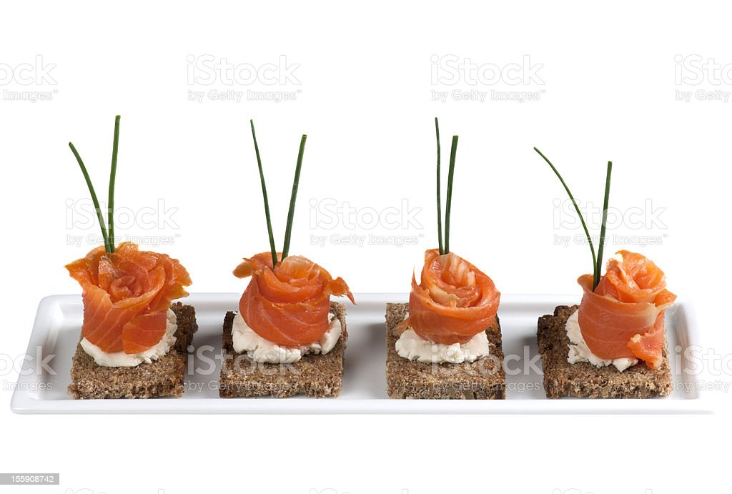 A row of garnished salmon canapes on a white platter stock photo