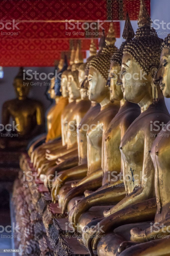 Row of golden Buddha statues in Thailand temple stock photo