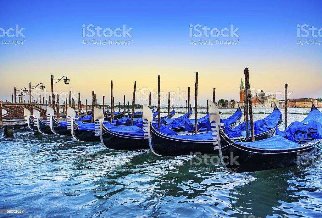 Row of gondolas at the sunset of Venice, Italy stock photo