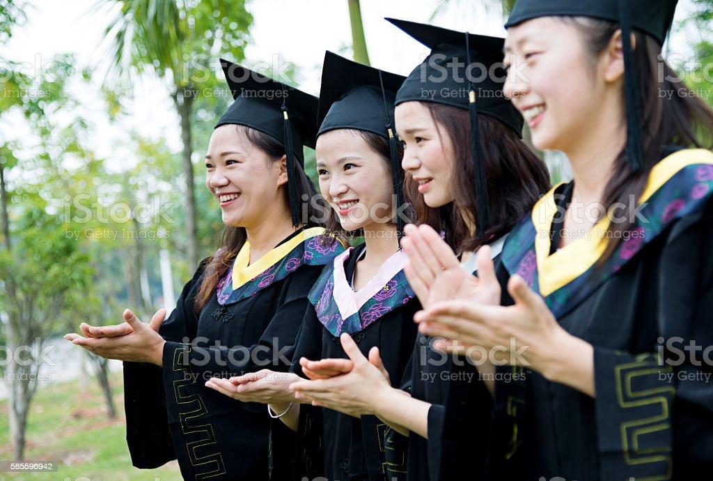 Row of graduates clapping stock photo