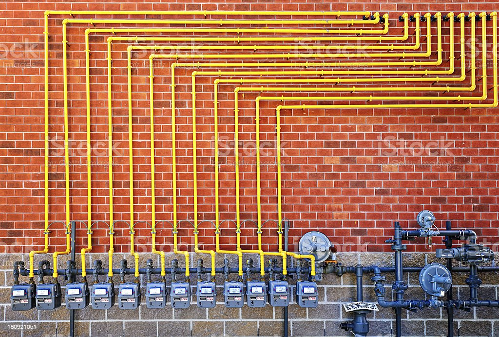 Row of gray has meters with yellow pipe on red brick wall stock photo