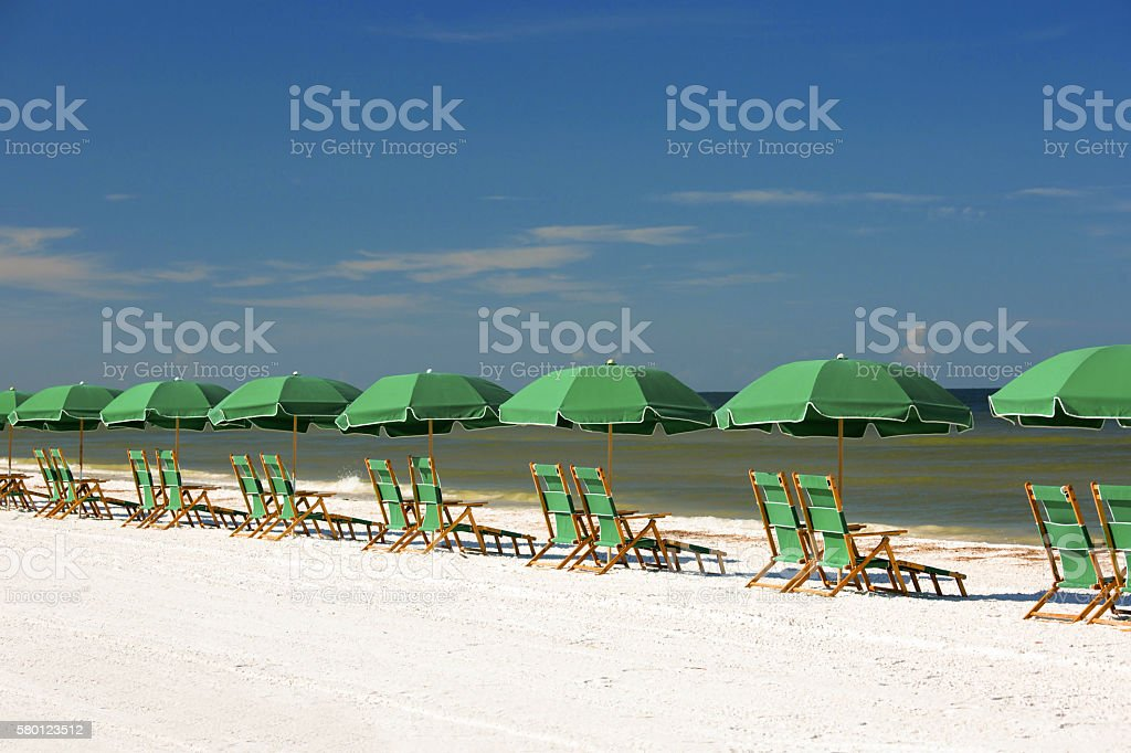 Row of green umbrellas and chairs facing the surf stock photo