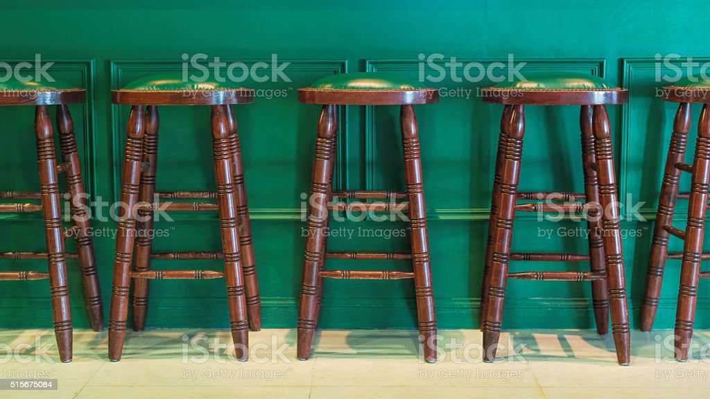 Row of green wooden stools stock photo