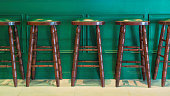 Row of green wooden stools