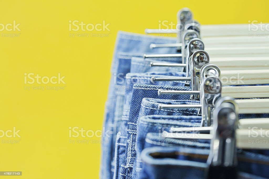 Row of hanged blue jeans stock photo