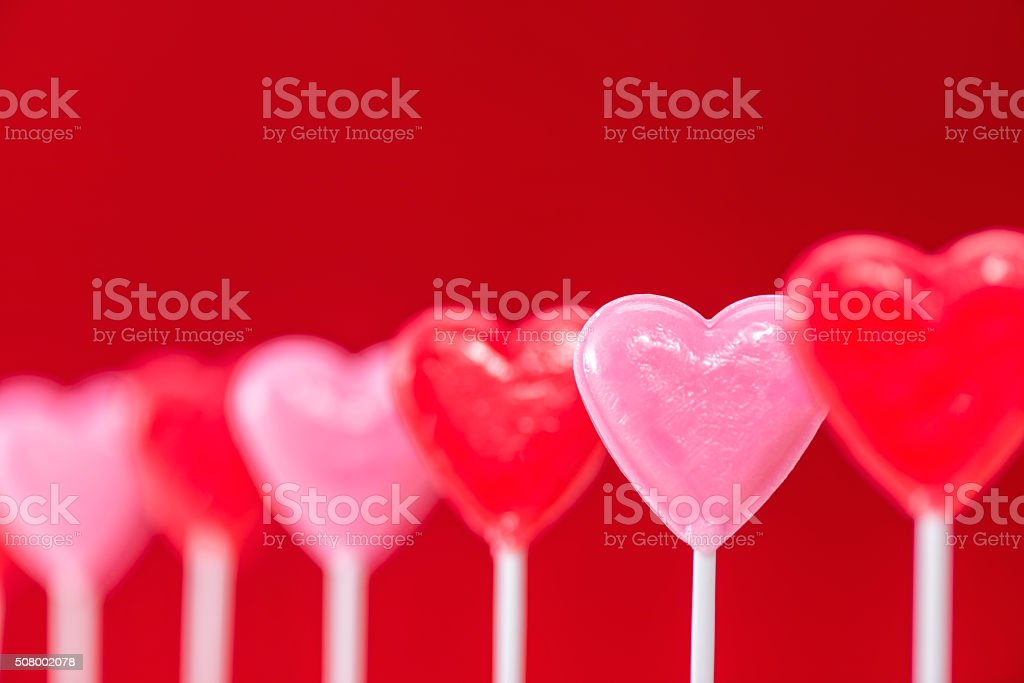 Row of heart shaped lollipops on red background stock photo