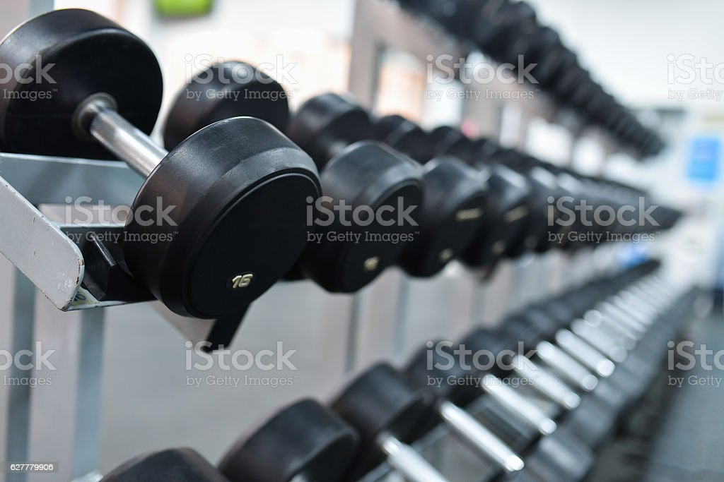 Row of heavy iron dumbbells on a rack at gym stock photo