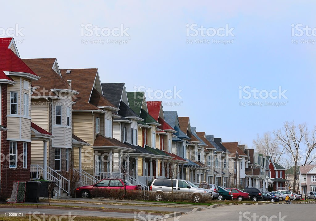 A row of houses with cars parked in a suburban neighborhood stock photo