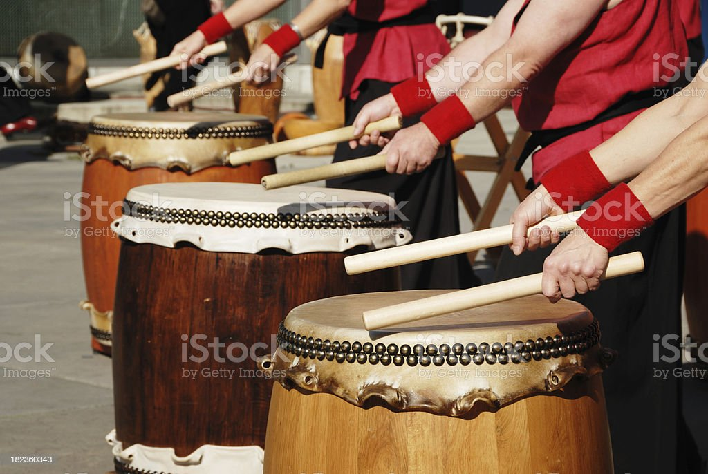 row of japanese drums and hands with sticks royalty-free stock photo