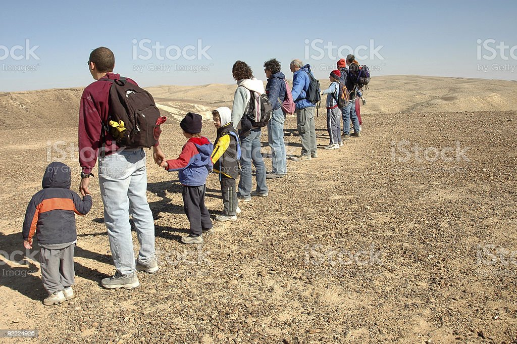 Row of kids and adults holding hands in Negev Desert, Israel stock photo