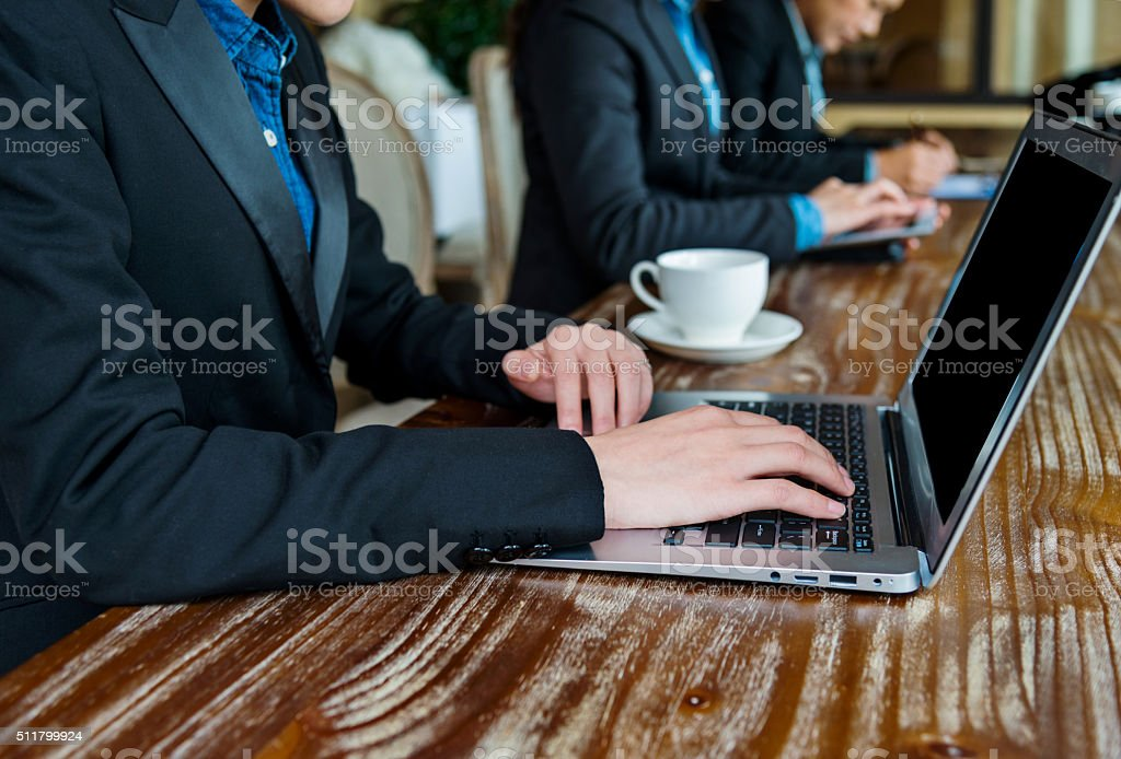 Row of laptops with hands stock photo