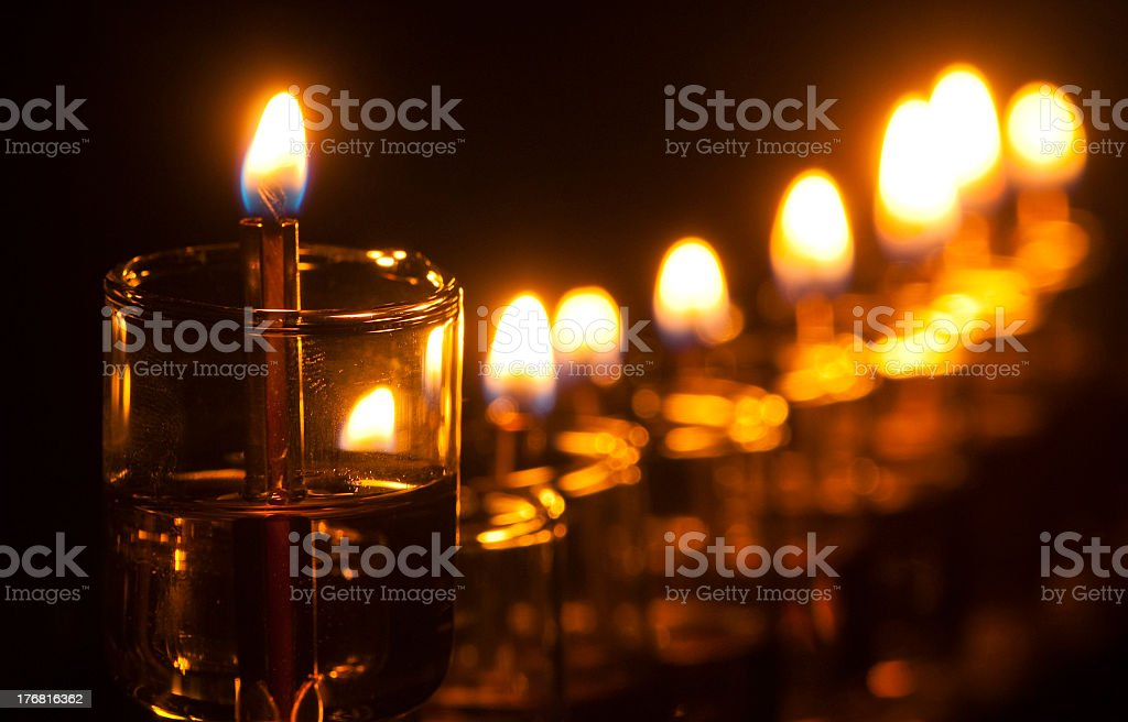 Row of lit Hanukkah oil menorah candles royalty-free stock photo