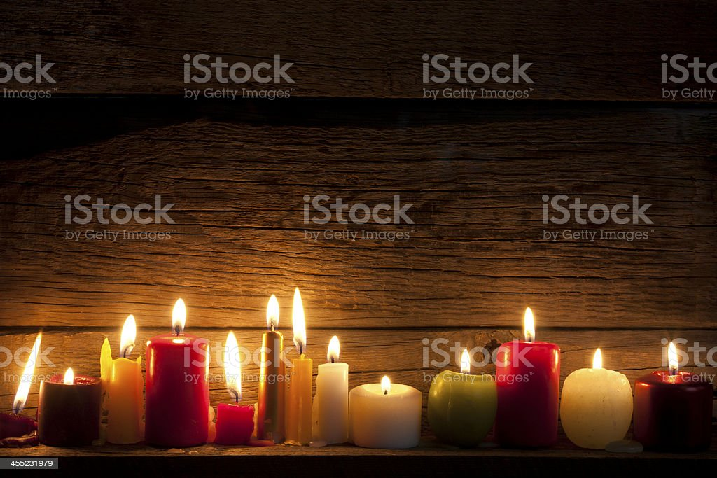 A row of lit mismatched candles on vintage wood wall shelf stock photo