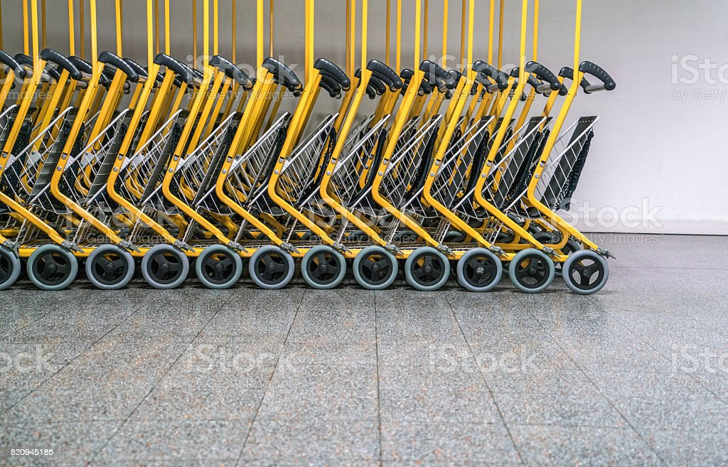 Row of luggage carts in airport stock photo