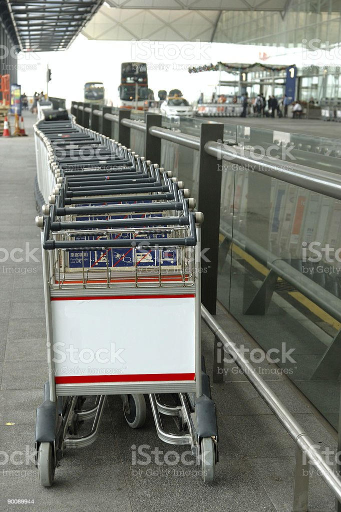 Row of luggage carts with blank billboard royalty-free stock photo