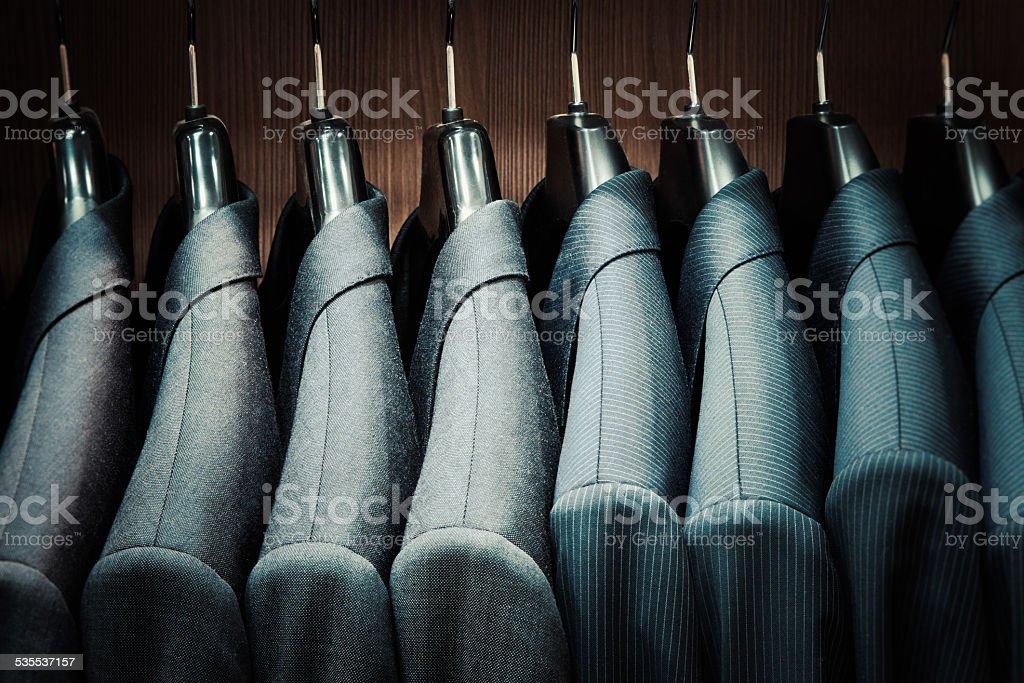 Row of men suit jackets on hangers stock photo