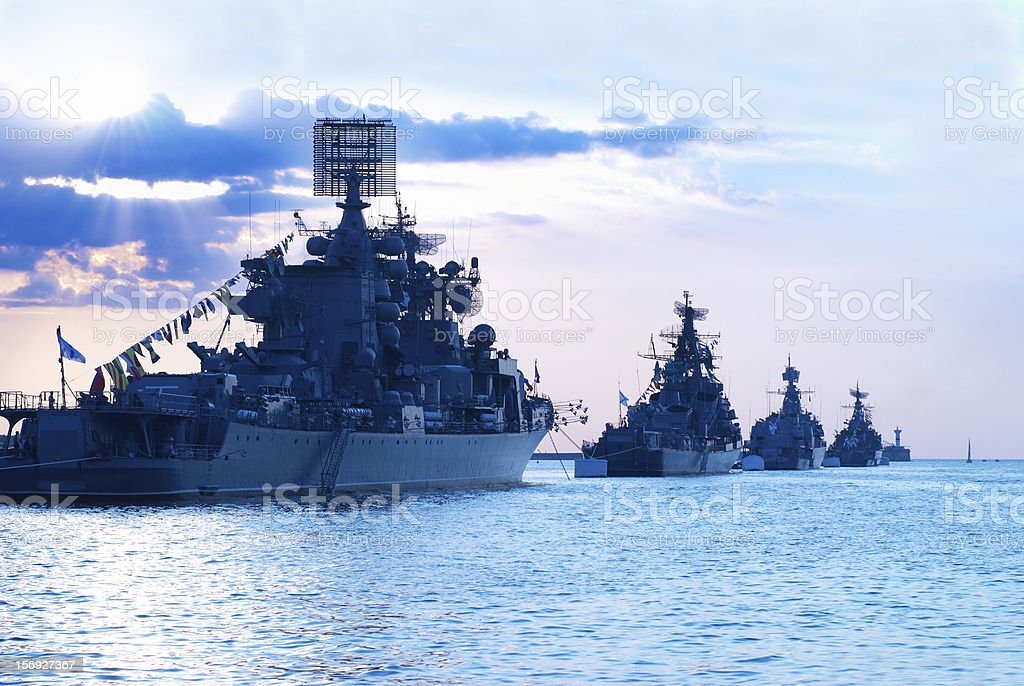 Row of military ships at the sea during sunset stock photo