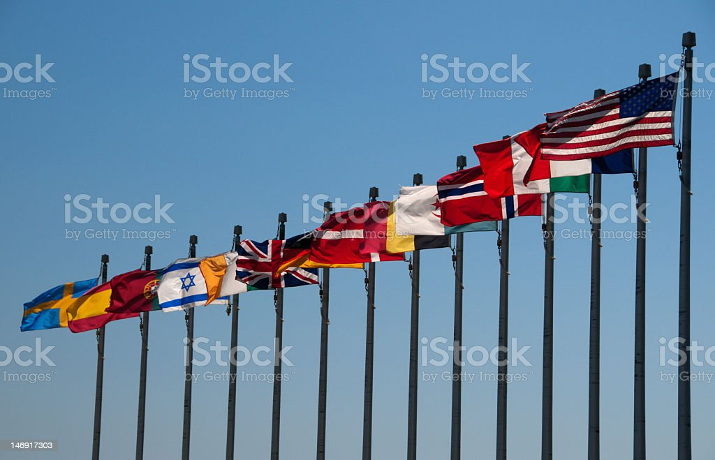 A row of multi national flags blowing in the wind under sky stock photo