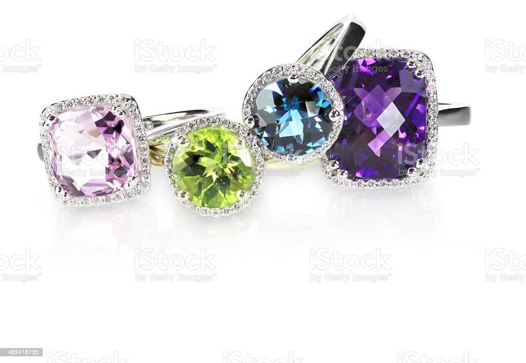 Row of multicolored rainbow diamond halo gemstone rings stock photo