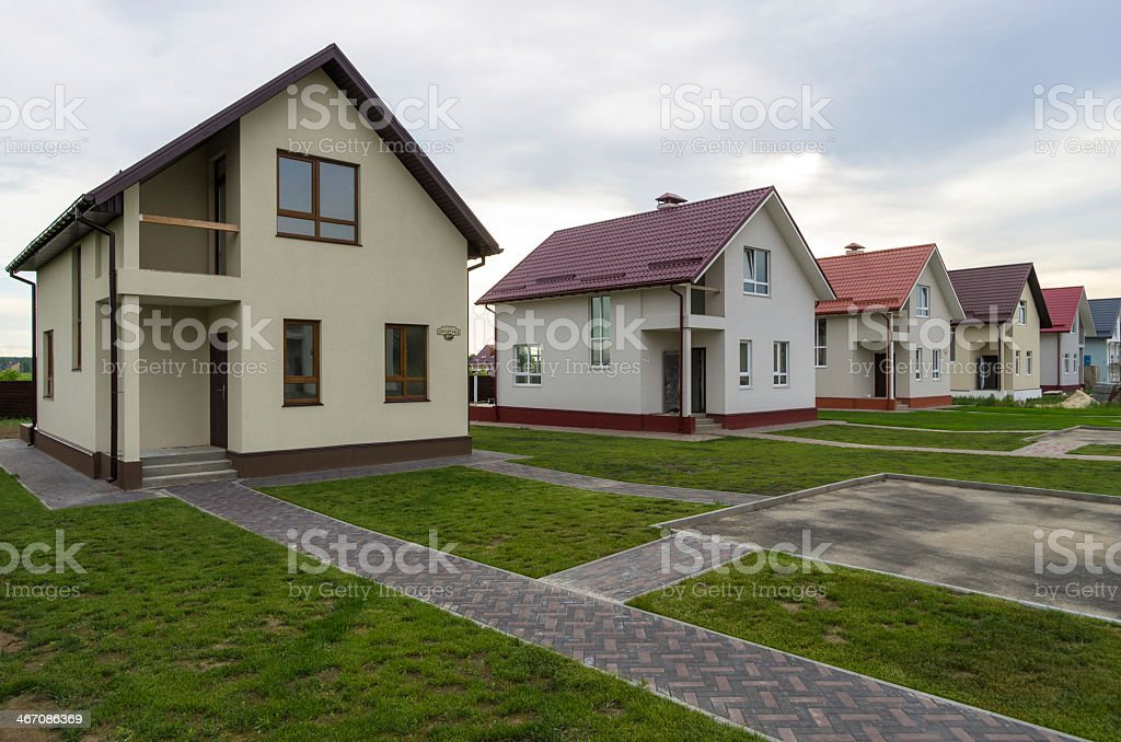 A row of newly built cottages surrounded by grass stock photo
