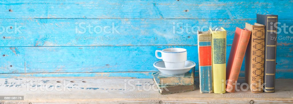 row of old books with a cup of coffee stock photo