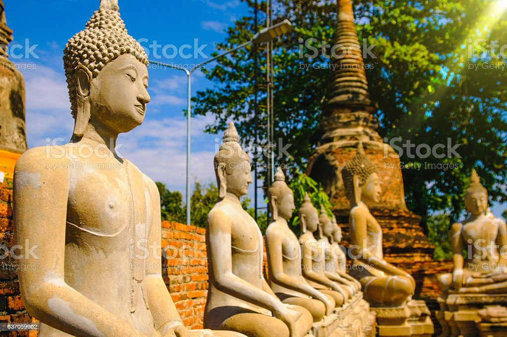 Row of old Buddha Statues with Blue Sky background stock photo