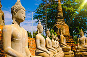 Row of old Buddha Statues with Blue Sky background