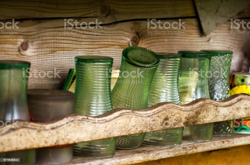 Row of old glasses on the wooden shelf stock photo