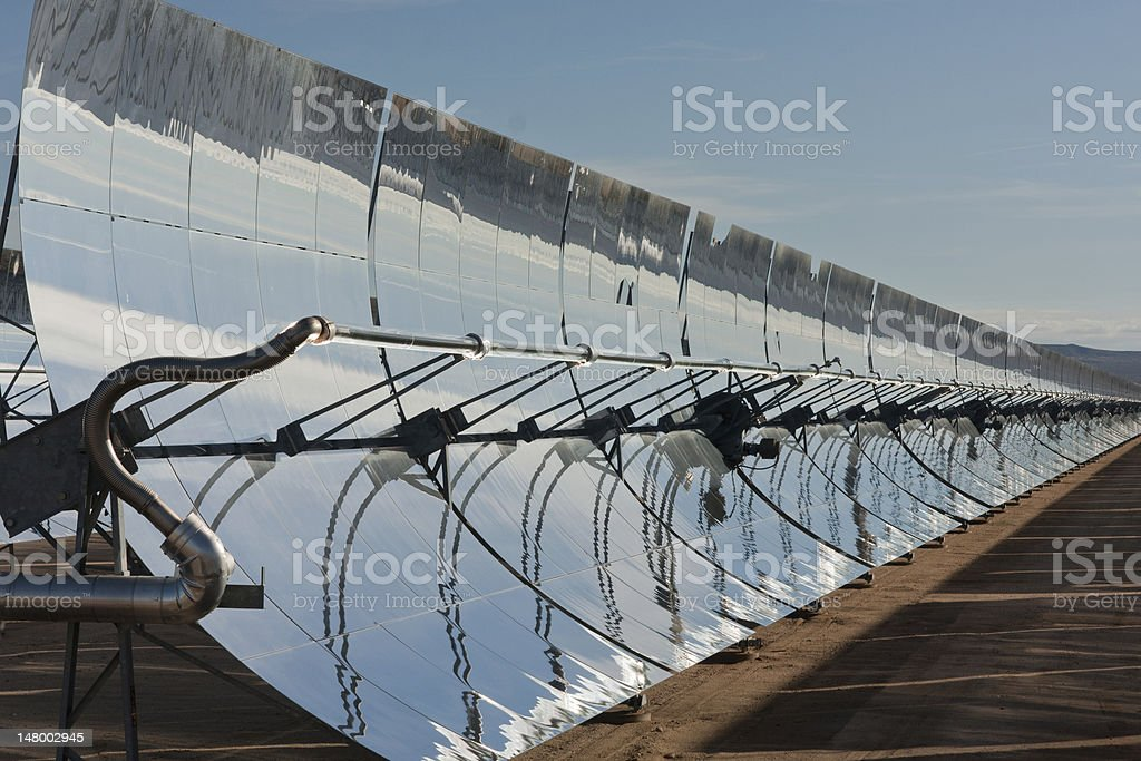 Row of parabolic mirrors facing the sun stock photo
