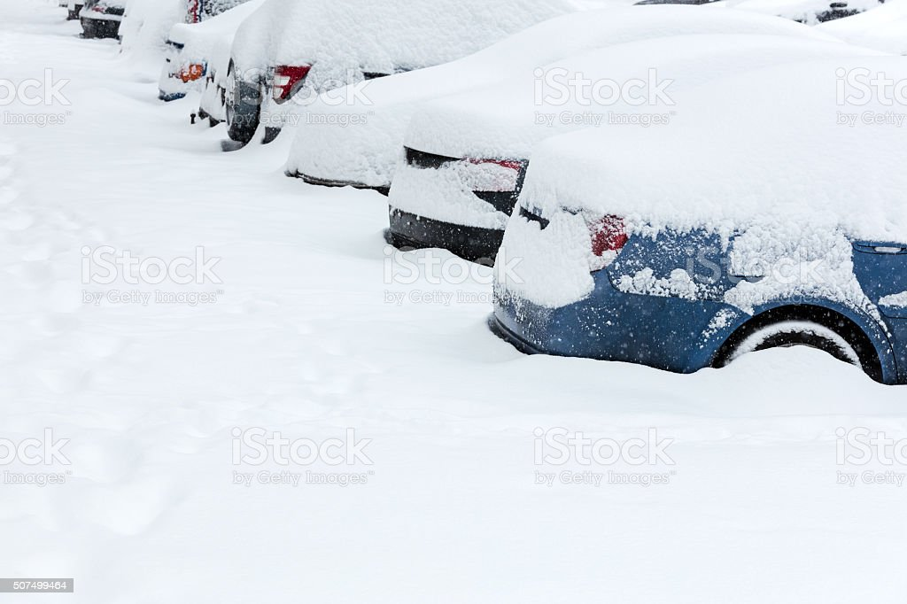 row of parked cars under snow stock photo