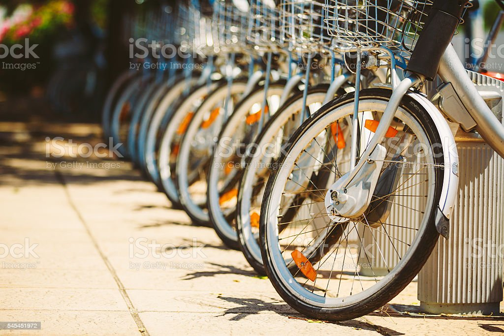 Row of parked vintage bicycles bikes for rent on sidewalk. stock photo