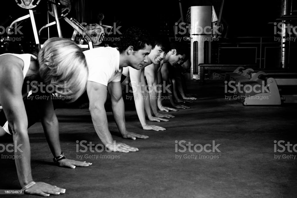 Row Of People Doing Push Ups At The Gym royalty-free stock photo