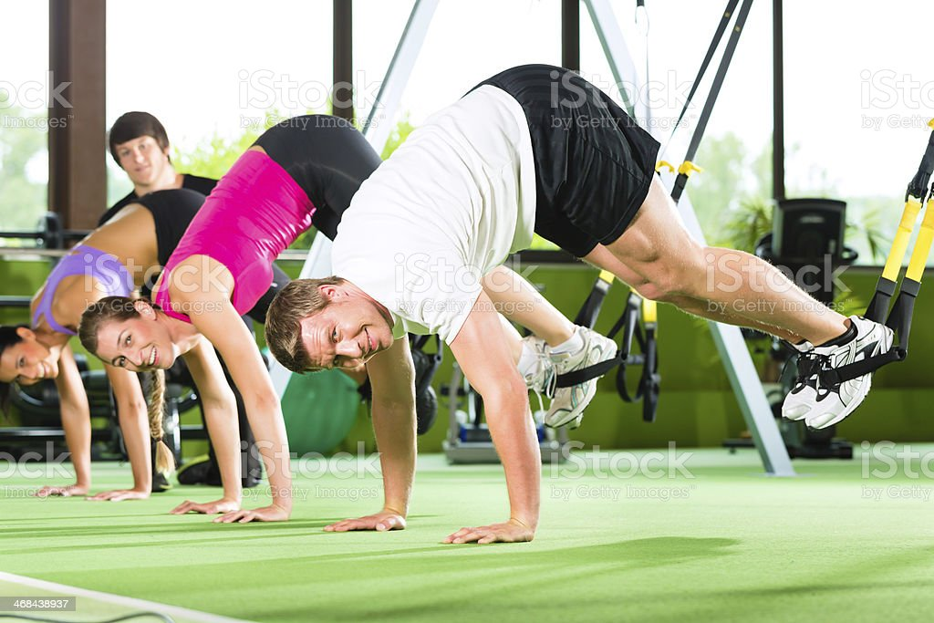 Row of people in the gym on a suspension training machine stock photo