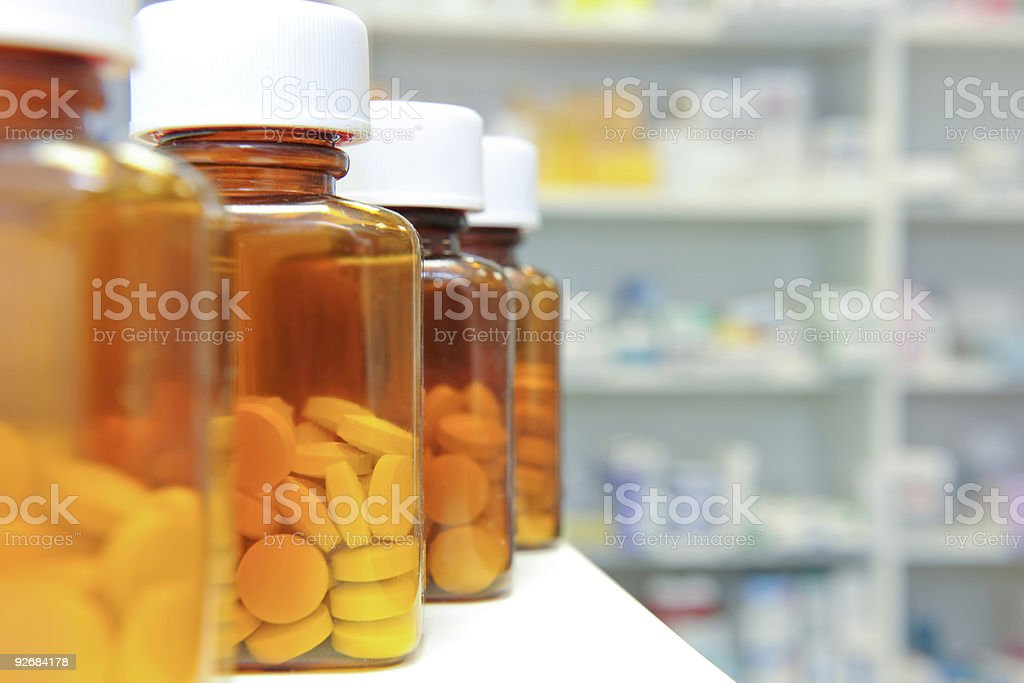 A row of pill bottles on a pharmacy counter stock photo