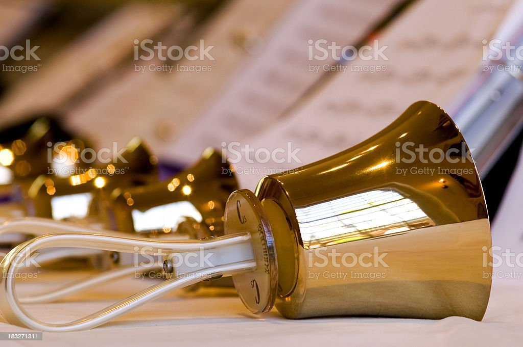 Row of polished brass handbells with sheet music stock photo