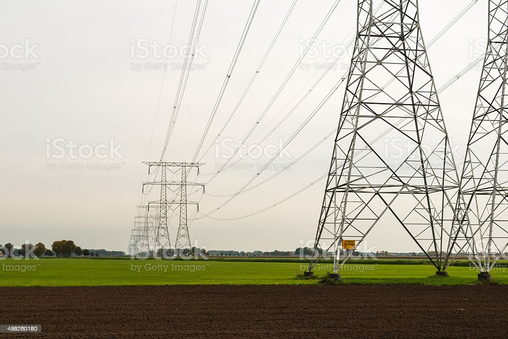 Row of power pylons in an agricultural area stock photo