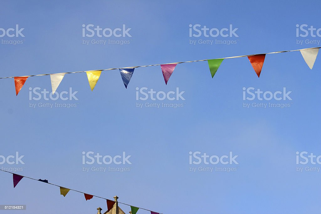 Row of rainbow coloured bunting flags on rope, against blue-sky stock photo
