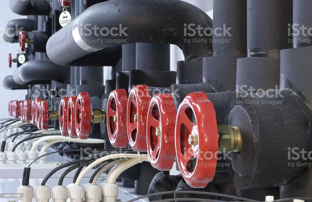 Row of red handles on large pipe work royalty-free stock photo