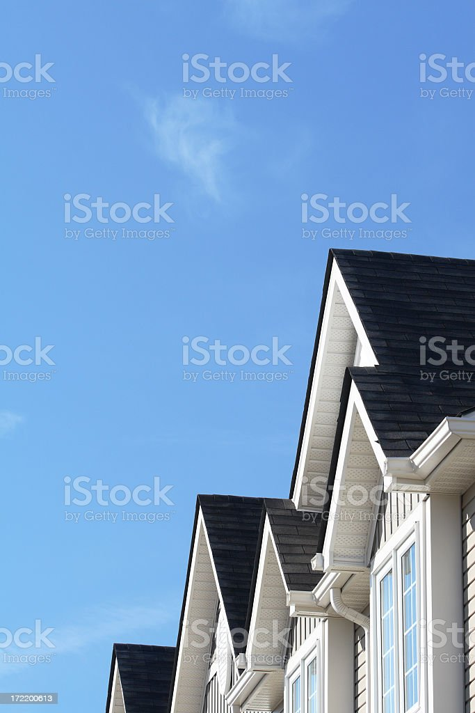 Row of roofs and eaves of homes with blue sky stock photo
