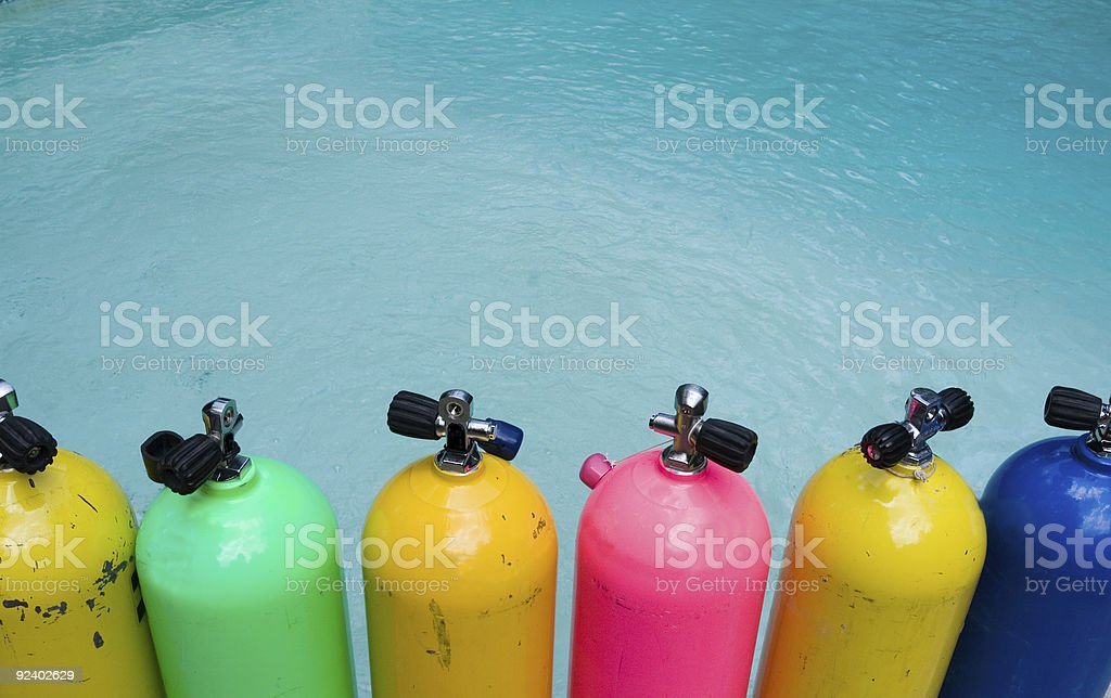 Row of Scuba Tanks Sitting in Front of Water stock photo