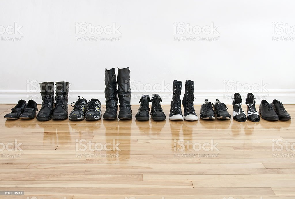 Row of shoes and boots on a wooden floor stock photo