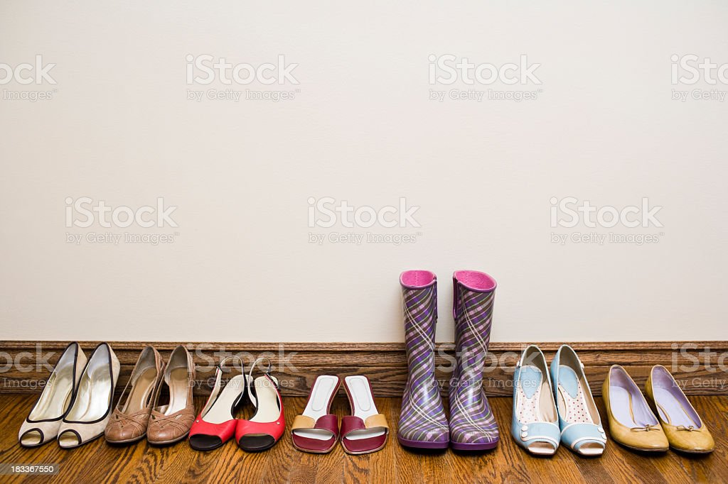 A row of shoes from heels to rain boots stock photo
