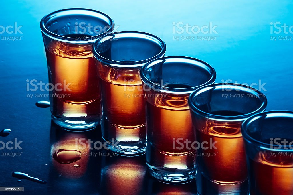 A row of shot glasses filled with liquor stock photo