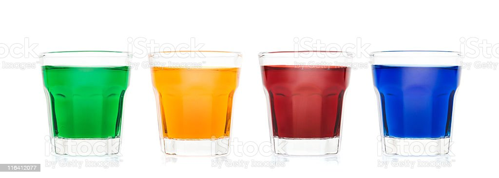 Row of shot glasses with colored drink on white royalty-free stock photo