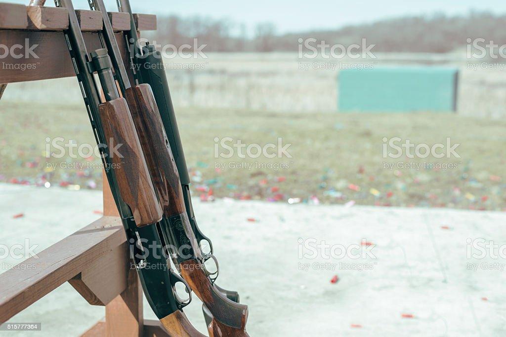 row of shotgun rifles on rack at shooting range stock photo