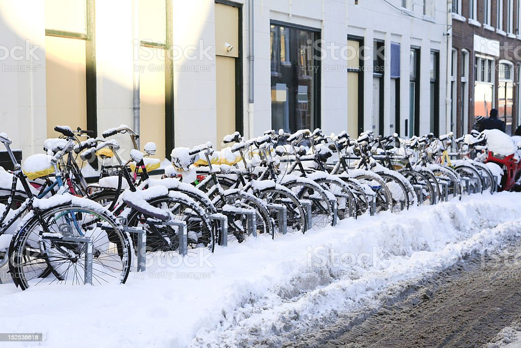 Row of snowcovered bikes stock photo