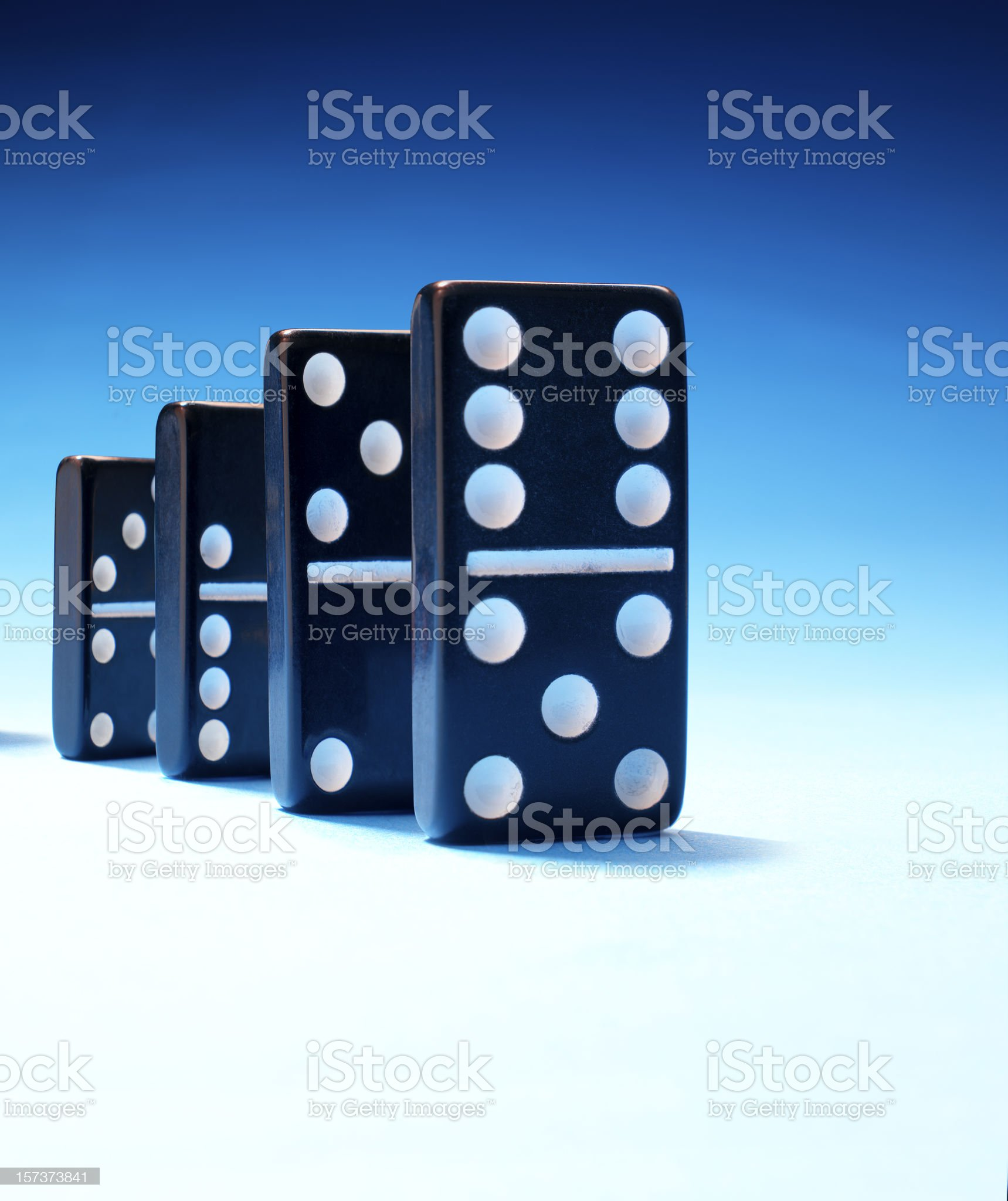 Row of standing black dominoes on blue background royalty-free stock photo